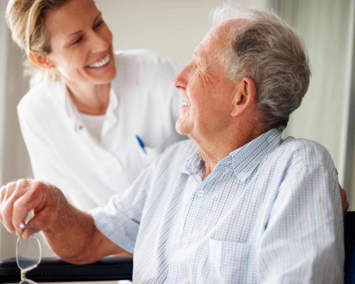 skilled nurse and senior man smiling